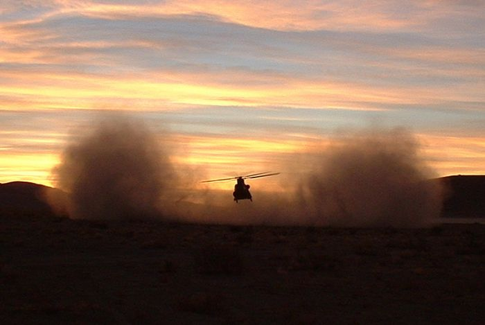"82-23768 - a CH-47D Chinook helicopter, belonging to C Company - ""Flippers"", 159th Aviation Regiment, located at Fort Bragg, North Carolina - shakes off the dust at sunrise in the National Training Center (NTC), January 2002."