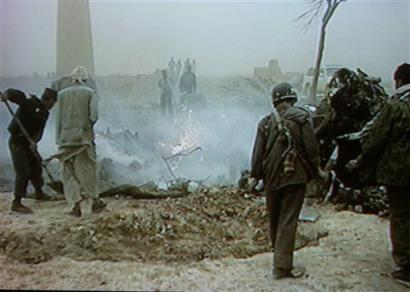 In this image taken from video, Afghans inspect the wreckage of a U.S. military CH-47D Chinook helicopter.