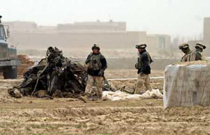 7 April 2005: U.S. troops walk past the wreckage of a U.S. military CH-47D Chinook helicopter that crashed in Ghazni province, southwest of Kabul. The crash killed 18 people a U.S. military spokeswoman said on Thursday.